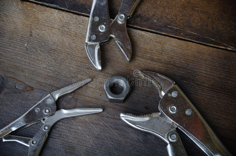 Close up locking pliers on wooden background, Hand tools in work shop.  royalty free stock photography