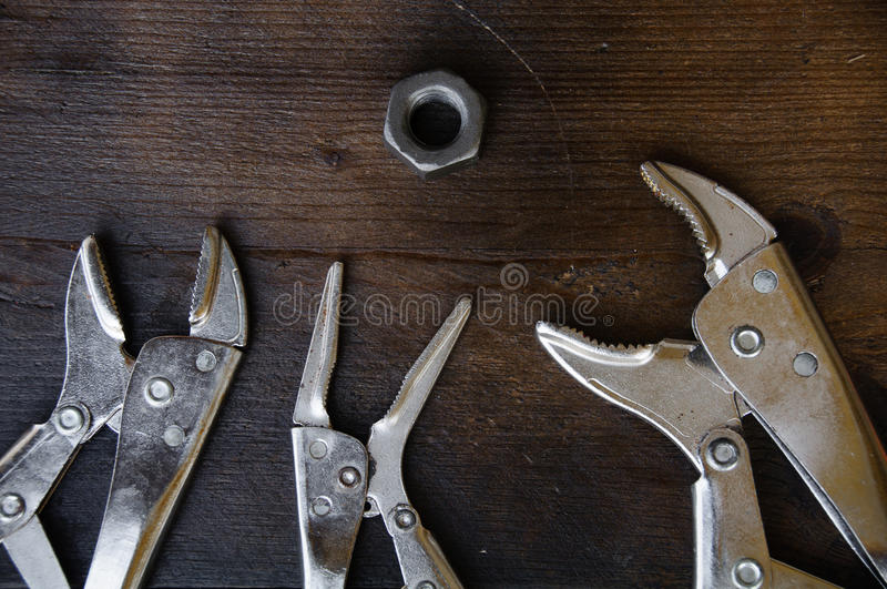 Close up locking pliers on wooden background, Hand tools in work shop.  stock photos