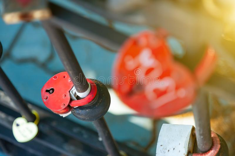 Close-up on locks of hearts in different colors and shapes hanging on the fence as a sign of eternal love, which is hung during stock photos