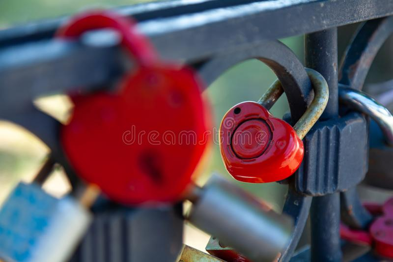 Close-up on locks of hearts in different colors and shapes hanging on the fence as a sign of eternal love, which is hung during royalty free stock images