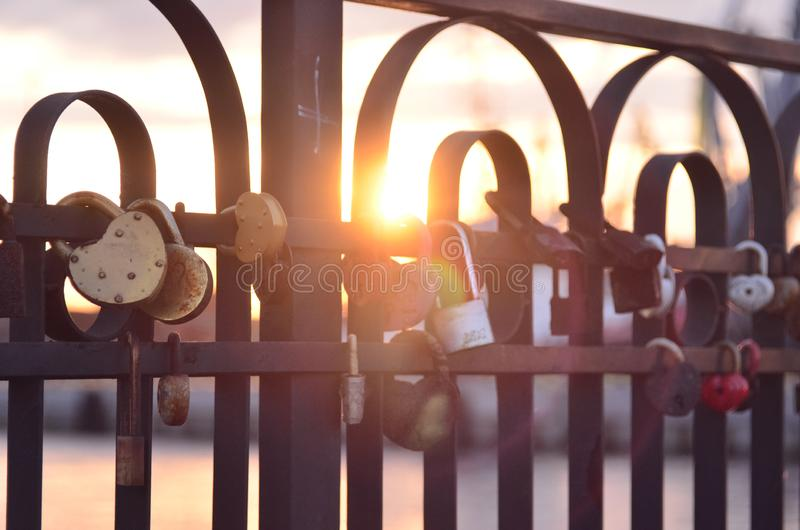 Close-up on locks of hearts in different colors and shapes hanging on the fence as a sign of eternal love, which is hung during royalty free stock photos
