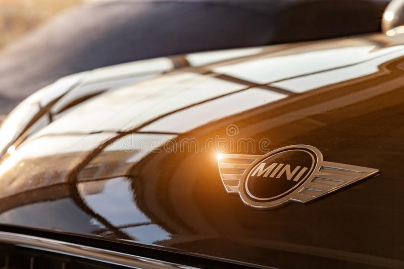 A close-up logo with a mini black metal chrome image on a brown shiny hood in the sunlight of a brown car as a symbol of an royalty free stock photography