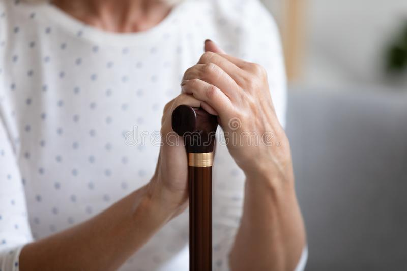 Close up lonely older woman holding hands on walking stick. Problem with health, sitting on couch and resting, older female using wooden cane during royalty free stock photos
