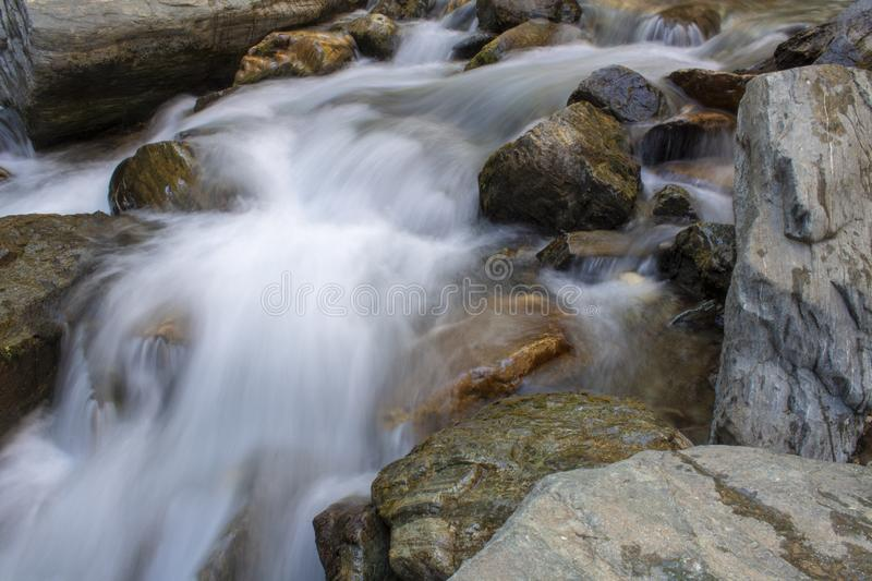 Close-up and long exposure of water flowing through rocks. Foggy image. Stream, rocky, wallpaper, landscape, splashing, waterfall, nature, river, smooth, creek stock photos