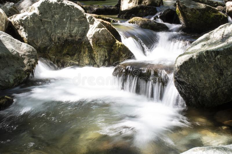Close-up and long exposure of water flowing through rocks. Foggy image. Stream, rocky, wallpaper, landscape, splashing, waterfall, nature, river, smooth, creek royalty free stock photo