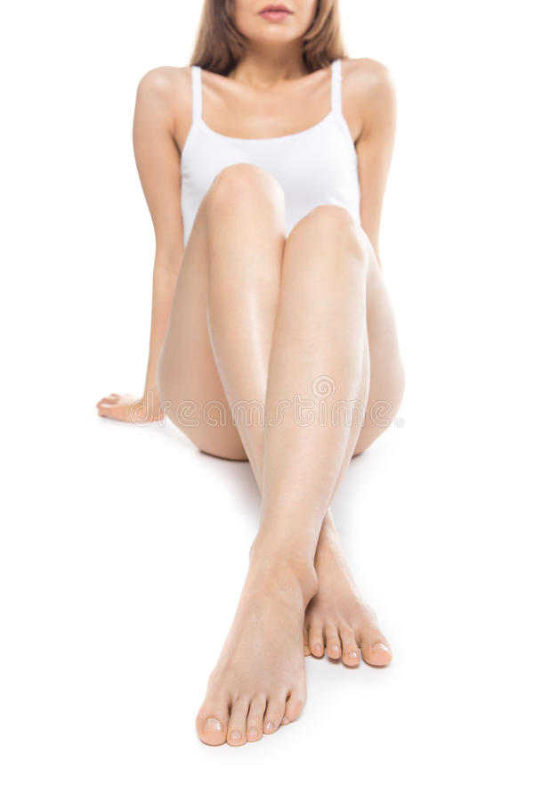 Close-up of long legs against white background. Close-up of long legs of beautiful attractive Caucasian young model sitting against white background. Pretty stock images