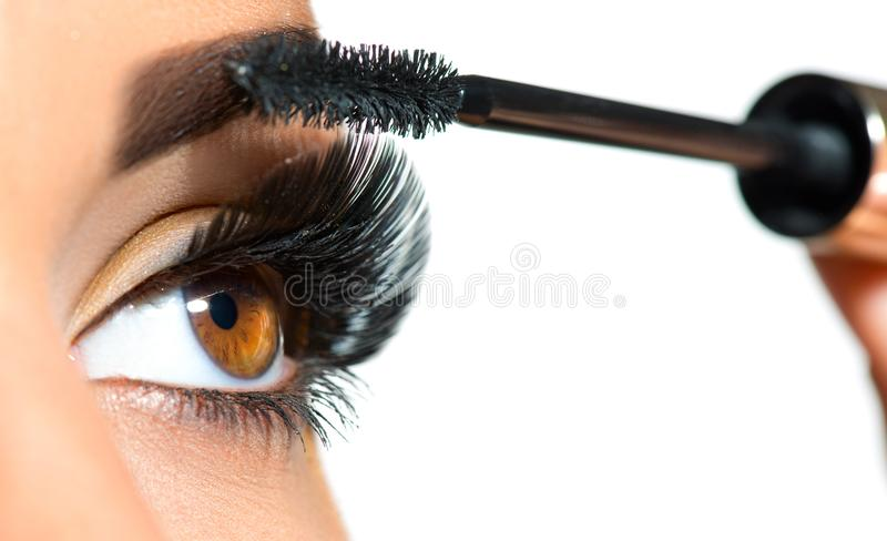 Close up longo dos chicotes Mulher bonita que aplica o rímel em seus olhos fotografia de stock