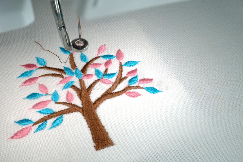 Close up look of embroider. Minimal tree brown stem cyan and pink leafs design on white cotton fabric in embroidery machine royalty free stock photo