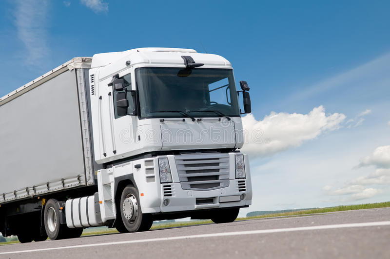 Close up lorry truck on road. White cabin and part of lorry truck body moving on road royalty free stock image