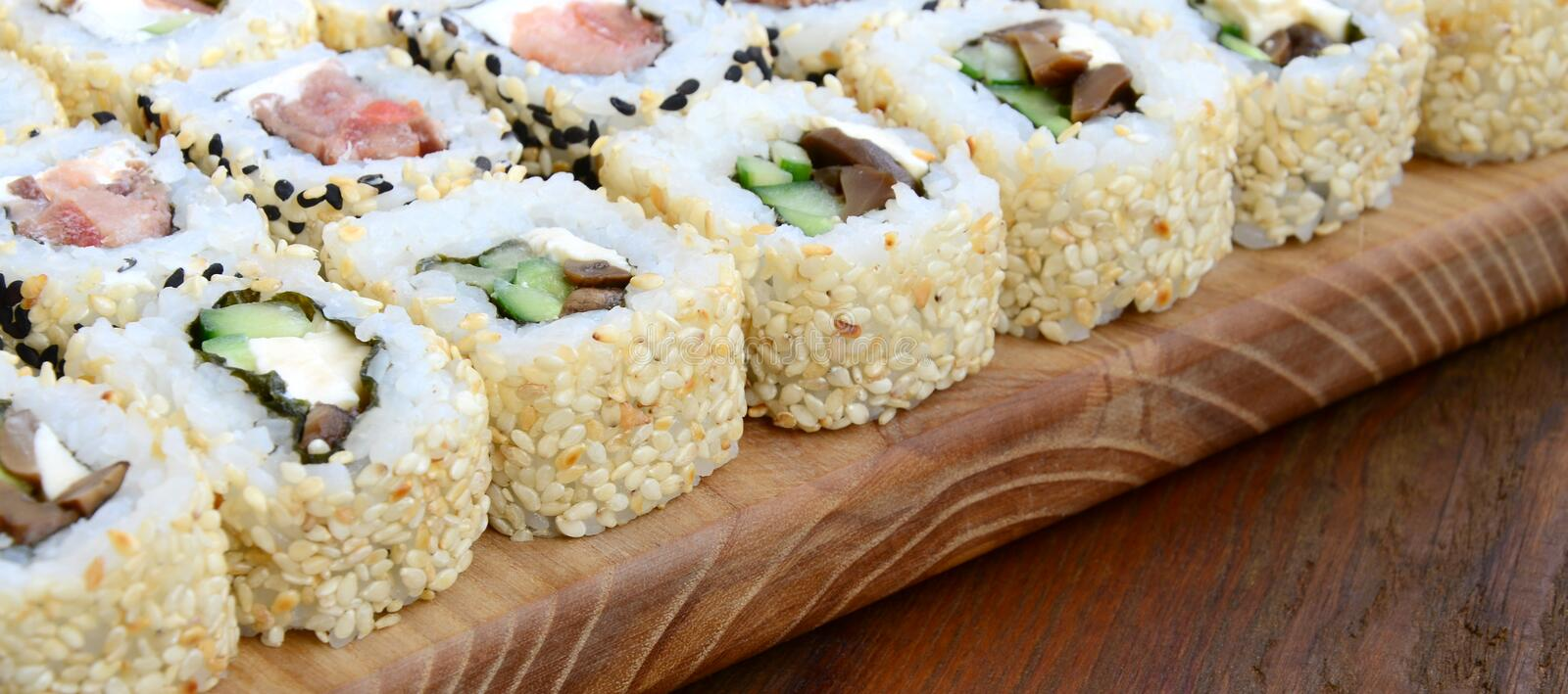 Close-up of a lot of sushi rolls with different fillings lie on a wooden surface. Macro shot of cooked classic Japanese food with stock photography