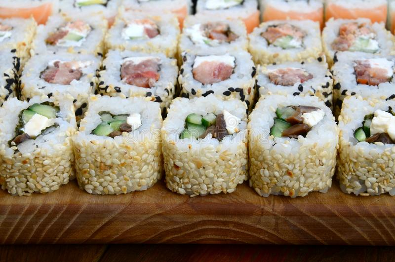 Close-up of a lot of sushi rolls with different fillings lie on a wooden surface. Macro shot of cooked classic Japanese food with stock photos