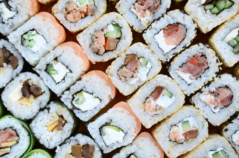 Close-up of a lot of sushi rolls with different fillings. Macro shot of cooked classic Japanese food. Background image.  royalty free stock image