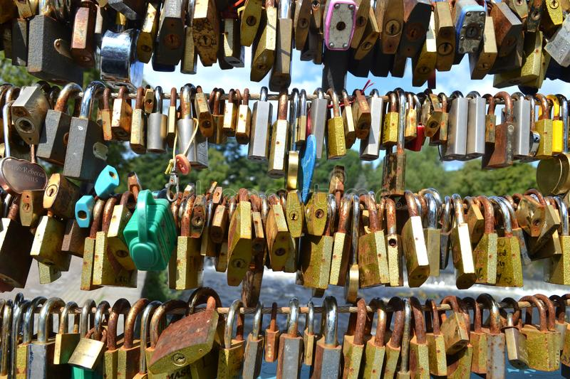 Close Up Of Lots Padlocks On Bridge. Foreground view of lots of rusty padlocks of different sizes and colours, placed on a bridge by lovers - a symbol of love stock images