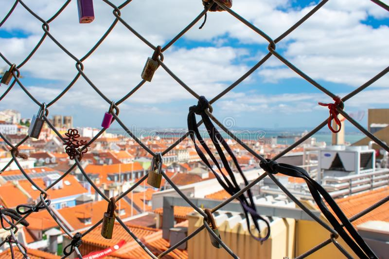 Close up on love lock in Lisbon Portugal. Aerial view of orange roofs buildings and sky stock photos
