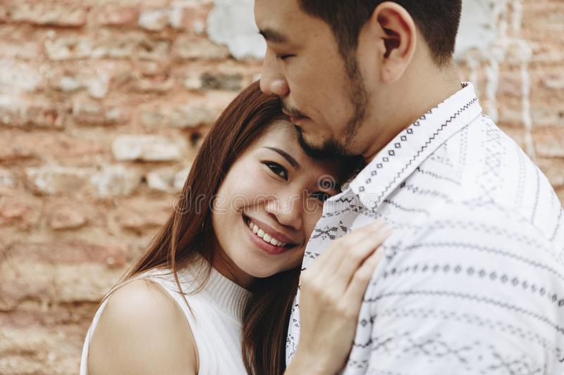 Lovely asian couple by a brick wall. Close up of lovely asian couple by a brick wall royalty free stock photos