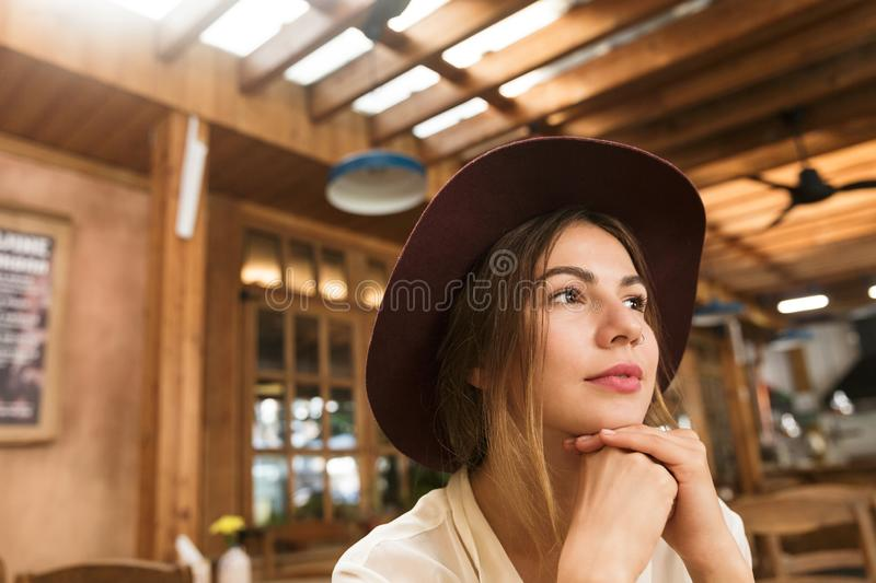 Close up of a lovely girl in hat sitting at the cafe table indoors stock images