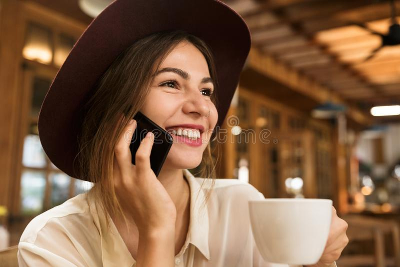 Close up of a lovely girl in hat sitting at the cafe table indoors, holding cup of tea, royalty free stock photography