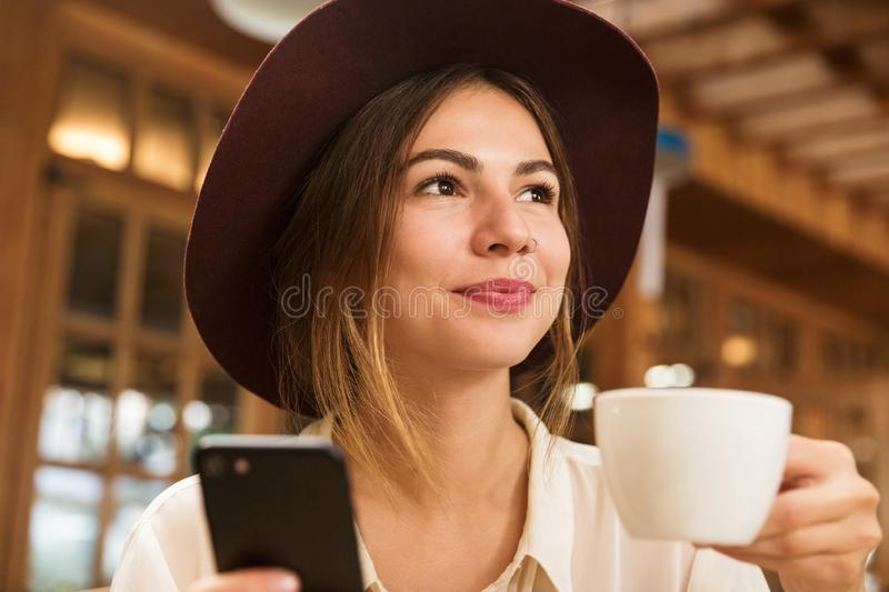 Close up of a lovely girl in hat sitting at the cafe table indoors, holding cup of tea royalty free stock photos