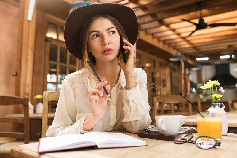 Close up of a lovely girl in hat sitting at the cafe table indoors, talking on mobile phone royalty free stock photo