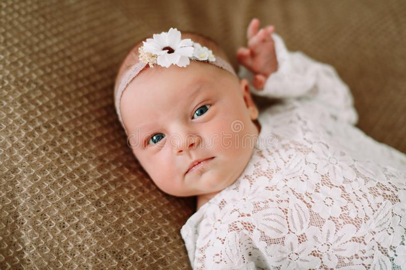 Close-up lovely newborn baby girl on a blanket. A portrait of a beautiful  newborn baby girl wearing a headband. Closeup photo. A lovely newborn baby girl on a royalty free stock photos