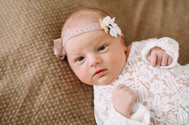 Close-up lovely newborn baby girl on a blanket. A portrait of a beautiful  newborn baby girl wearing a headband. Closeup photo. A lovely newborn baby girl on a stock photography