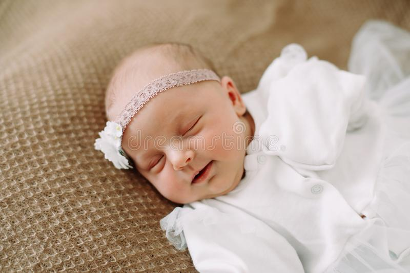 Close-up lovely newborn baby girl on a blanket. A portrait of a beautiful  newborn baby girl wearing a headband. Closeup photo. A lovely newborn baby girl on a royalty free stock photography