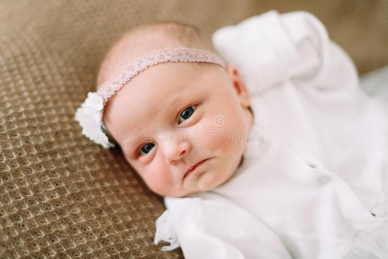 Close-up lovely newborn baby girl on a blanket. A portrait of a beautiful  newborn baby girl wearing a headband. Closeup photo. A lovely newborn baby girl on a stock image