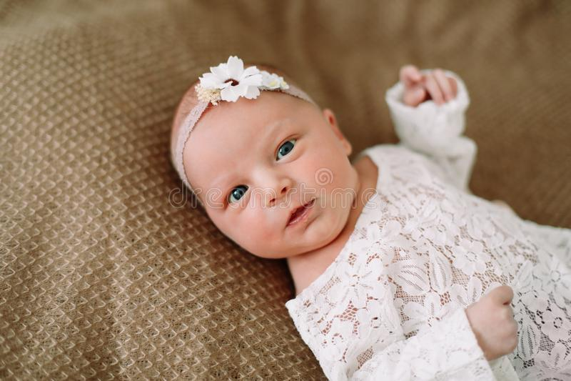Close-up lovely newborn baby girl on a blanket. A portrait of a beautiful  newborn baby girl wearing a headband. Closeup photo. A lovely newborn baby girl on a royalty free stock photo