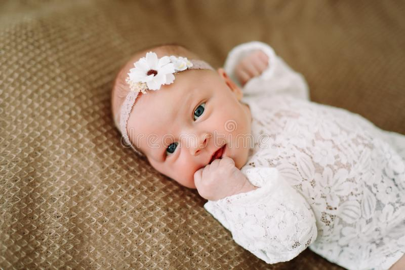 Close-up lovely newborn baby girl on a blanket. A portrait of a beautiful  newborn baby girl wearing a headband. Closeup photo. A lovely newborn baby girl on a royalty free stock image