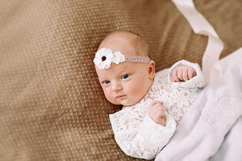 Close-up lovely newborn baby girl on a blanket. A portrait of a beautiful  newborn baby girl wearing a headband. Closeup photo. A lovely newborn baby girl on a stock photos