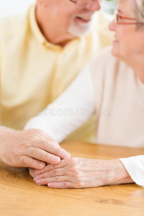 Close-up of lovely senior couple holding hands. Focus on the han stock images