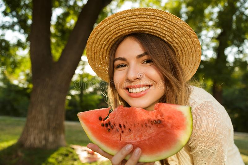 Close up of lovely young girl in summer hat spending time at the park, royalty free stock photography