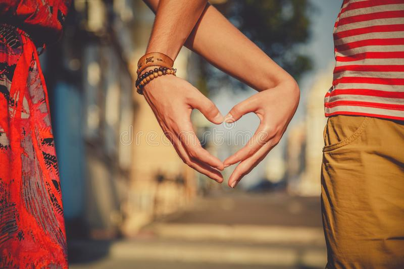 Close up of loving couple making heart shape with hands at city street. Summertime stock image