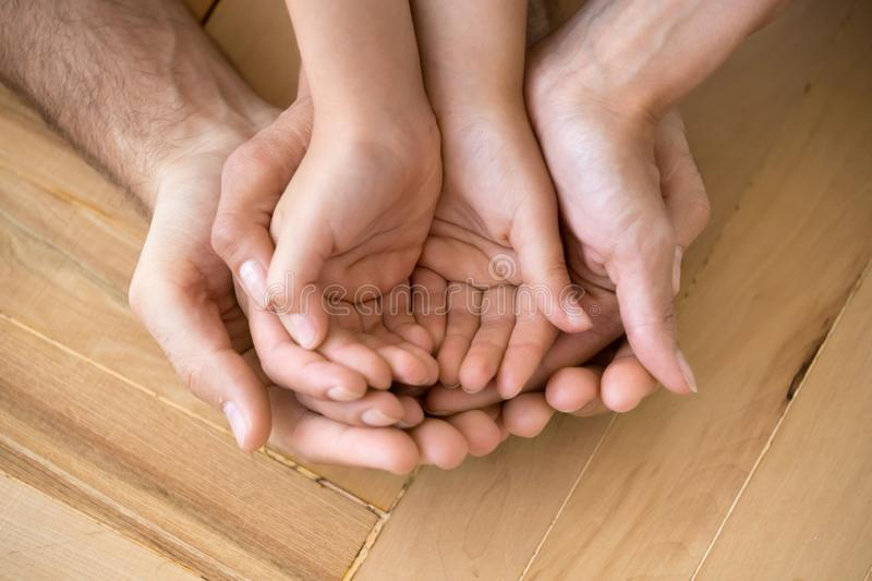 Close up of loving mom dad and kid hold hands on floor palms up royalty free stock image