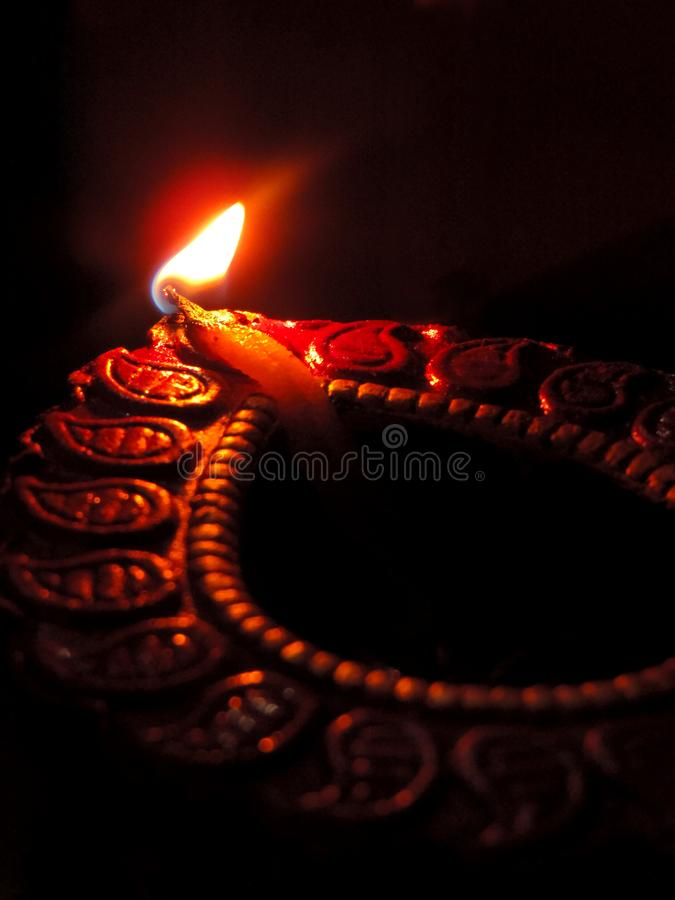 Close up low key indian dipavali oil clay lamp, chirag or panti, shot from side top down angle on a dark black background royalty free stock image
