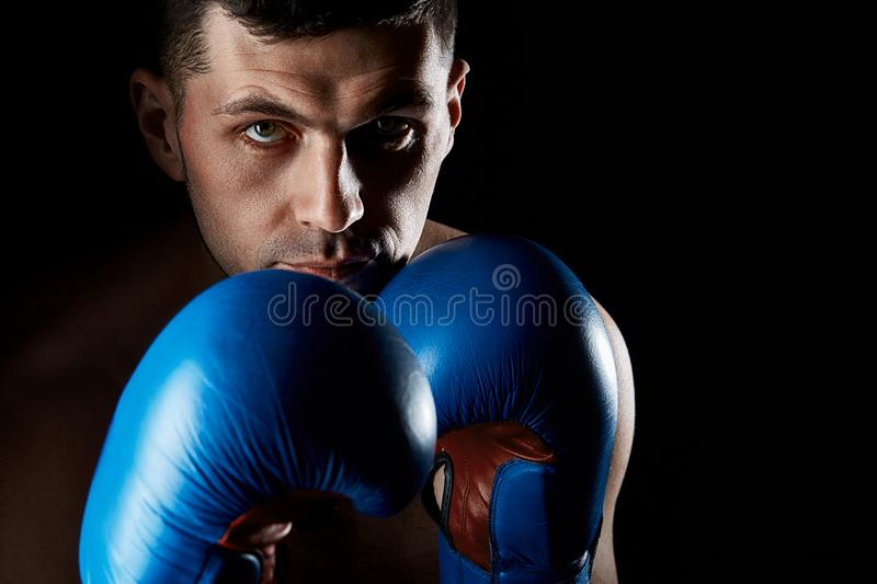 Close up low key portrait of an aggressive muscular fighter, showing his fist isolated on dark background. royalty free stock photos
