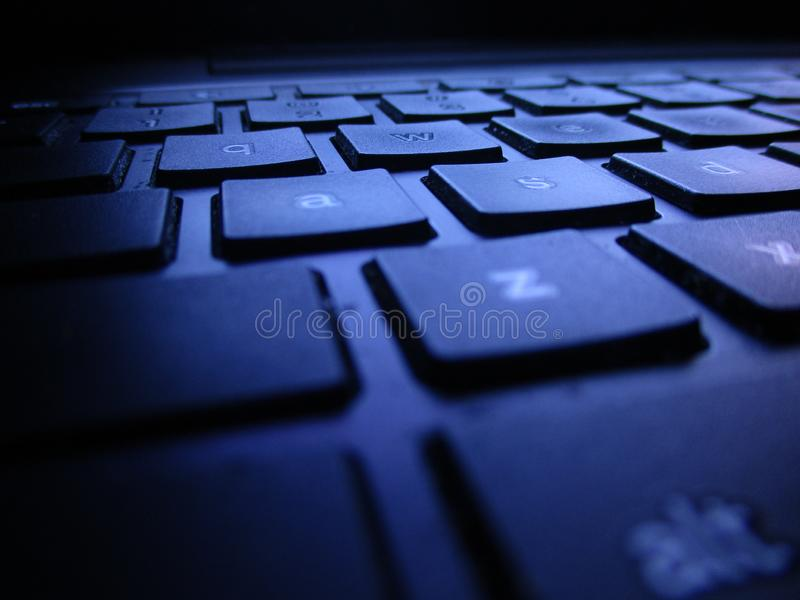Close Up Of Low Profile Keyboard Shot In Dark With Light From Computer Screen royalty free stock image