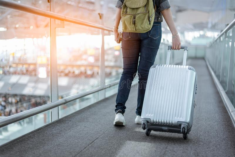 Close up lower body of woman traveler with luggage suitcase going to around the world by plane. Female tourist escalator stock photo