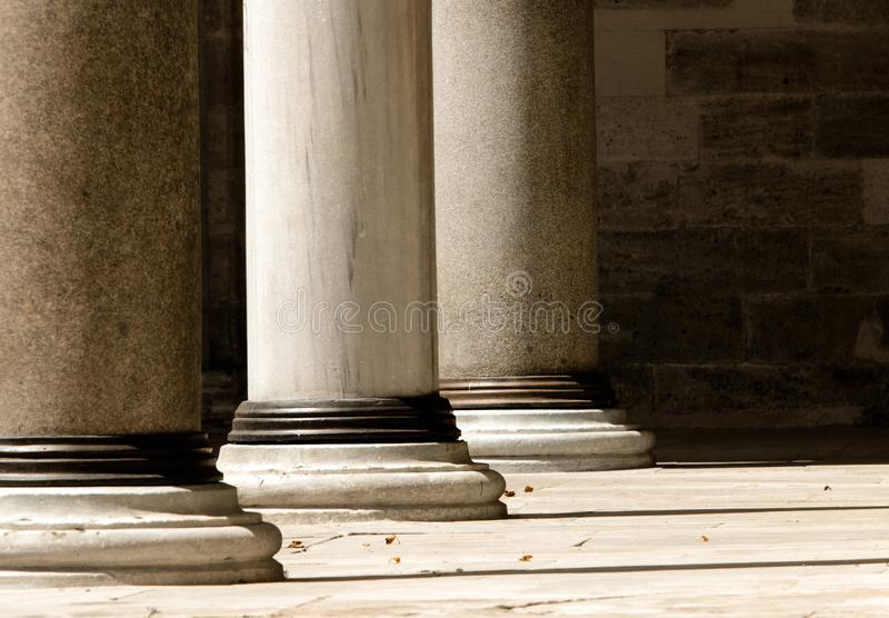 Close up of lower section of three doric order marble columns. Washed with sunlight in single point perspective image stock images