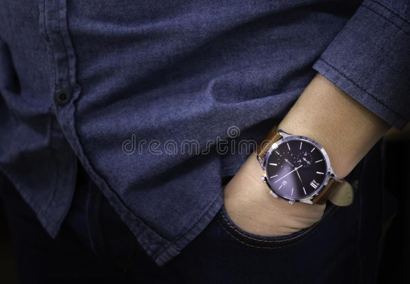 Close-up of luxury watch brown leather strap on wrist of man. Business man hand in pants pocket. His wearing blue jean shirt and navy blue jeans with casual stock images