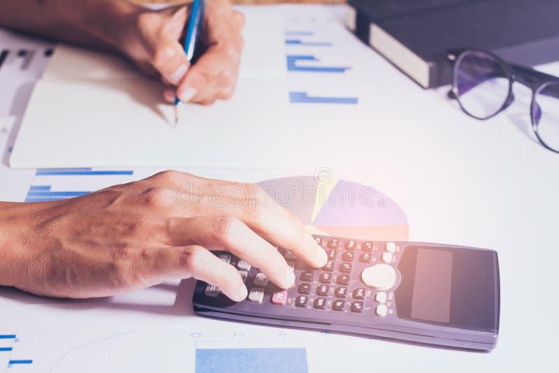 Close-up Mão da calculadora de trabalho do negócio ou da conta, lucro ou economia do gráfico na tabela do escritório domiciliário imagens de stock