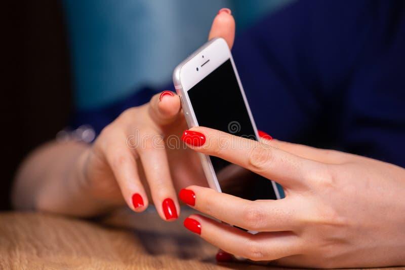 Close-up, m?os f?meas com tratamento de m?os vermelho para usar um smartphone em um fundo branco profundidade de campo limitada fotos de stock royalty free