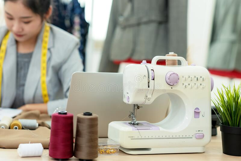 Close up machine designer. Asian young women fashion designer  working on her design in the showroom, royalty free stock photo