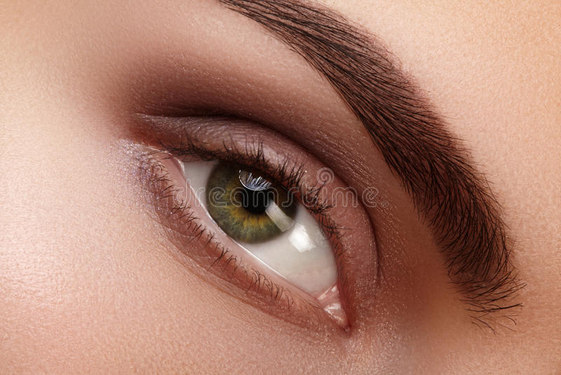Close-up macro beautiful female eye with perfect shape eyebrows. Clean skin, fashion natural smoky make-up. Good vision. Close-up macro of beautiful female eye stock photography