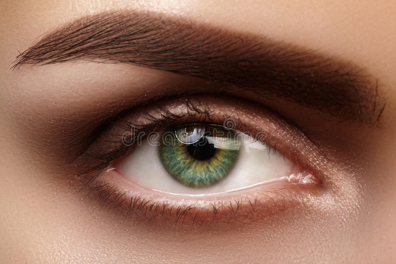 Close-up macro beautiful female eye with perfect shape eyebrows. Clean skin, fashion natural smoky make-up. Good vision royalty free stock photography
