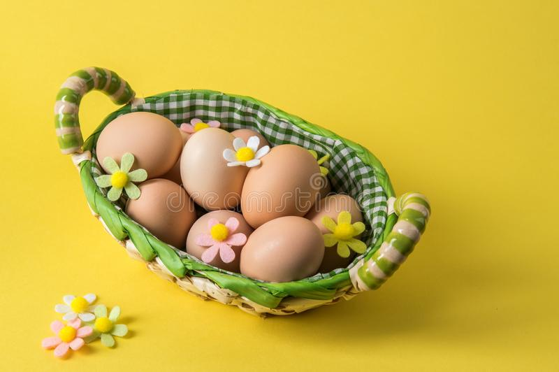 Close up. Easter. Rustic eggs in a wicker basket. The decor of the felt flowers of pastel colors. Yellow background. Copy space royalty free stock photo