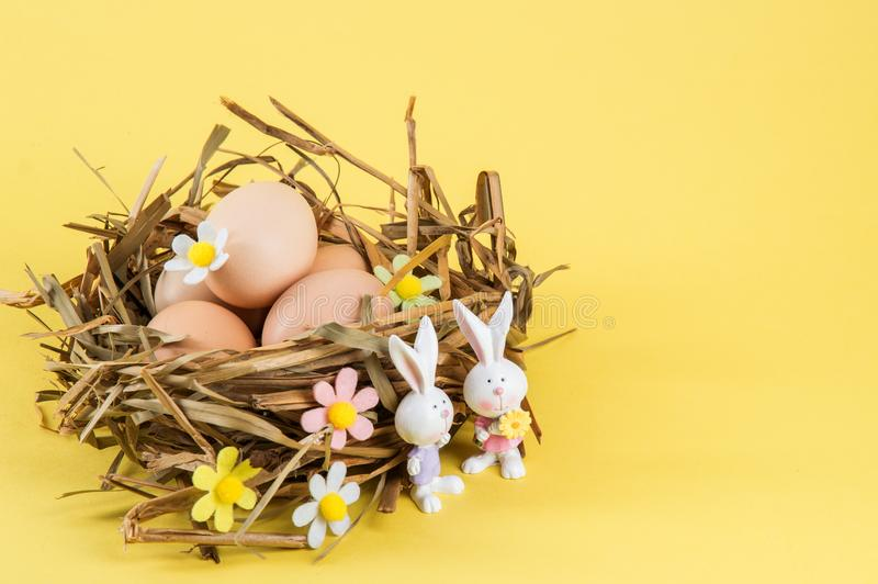 Close up. Easter still life. Farm eggs in a nest of straw. Two cute porcelain bunnies in the foreground. Yellow background. Copy stock image