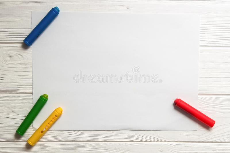 Close up, macro, flat lay. White background with a white sheet of paper. Crayons are scattered around. Copy space stock photography
