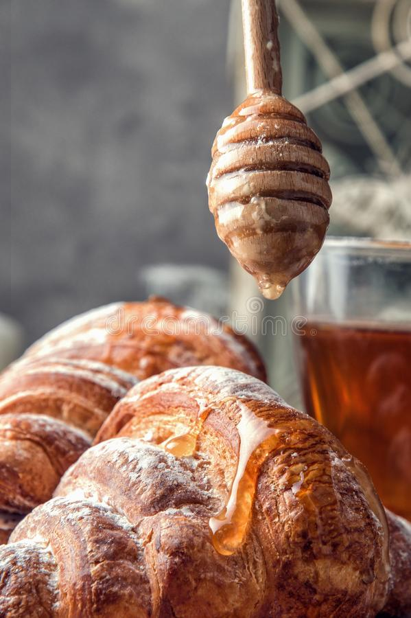 Close up. Freshly baked French croissants with a golden crisp. On top of the dessert flows, dripping golden honey or jam. royalty free stock images