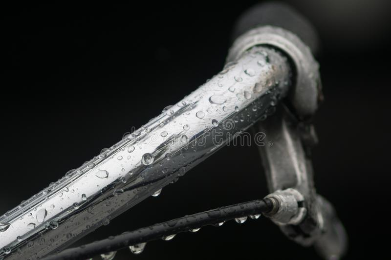 Close up / Macro image of bicycle handlebar in the rain with lots of water droplets on the steel. stock photos